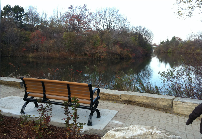 A wheel chair accessible park bench overlooking Lake Wabukayne in Mississauga