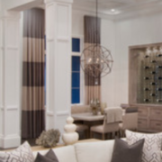 wide horizontal striped drapes in a monochromatic living room and dining room