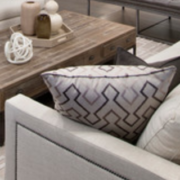Bold patterned accent pillows in a monochromatic living room